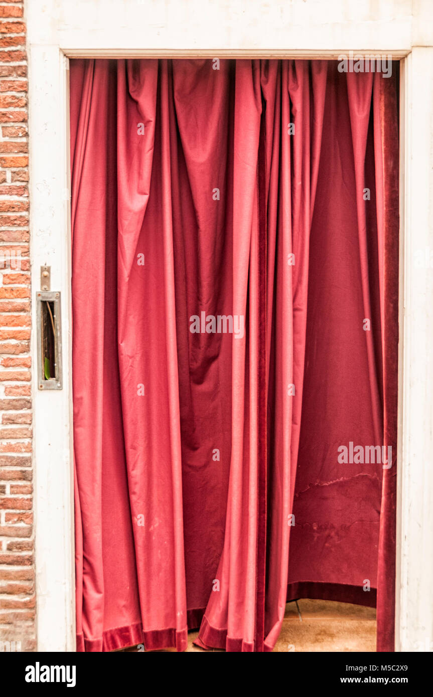 red curtain hung in a doorway - Stock Image