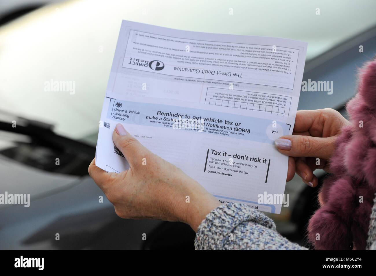 Woman checking her DVLA car vehicle Tax Renewal reminder notice - Stock Image