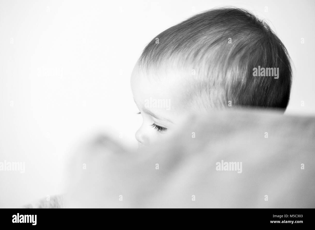 Cute baby girl toddler portrait playing hide and seek - Stock Image