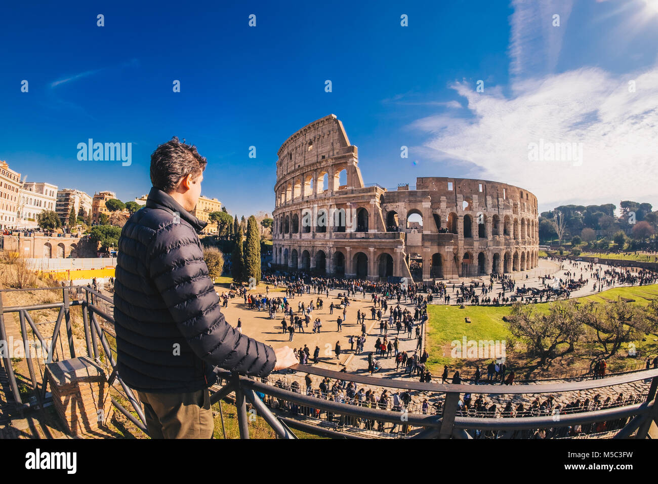 Male tourist enjyoing the view at the Colosseum in Rome, Italy - Stock Image