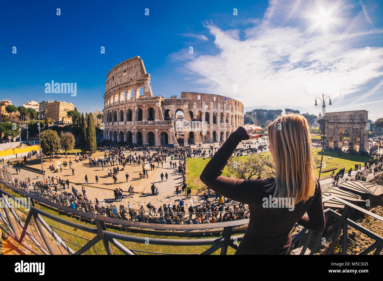 Woman tourist looking at the Roman Colosseum in Rome, Italy - Stock Image