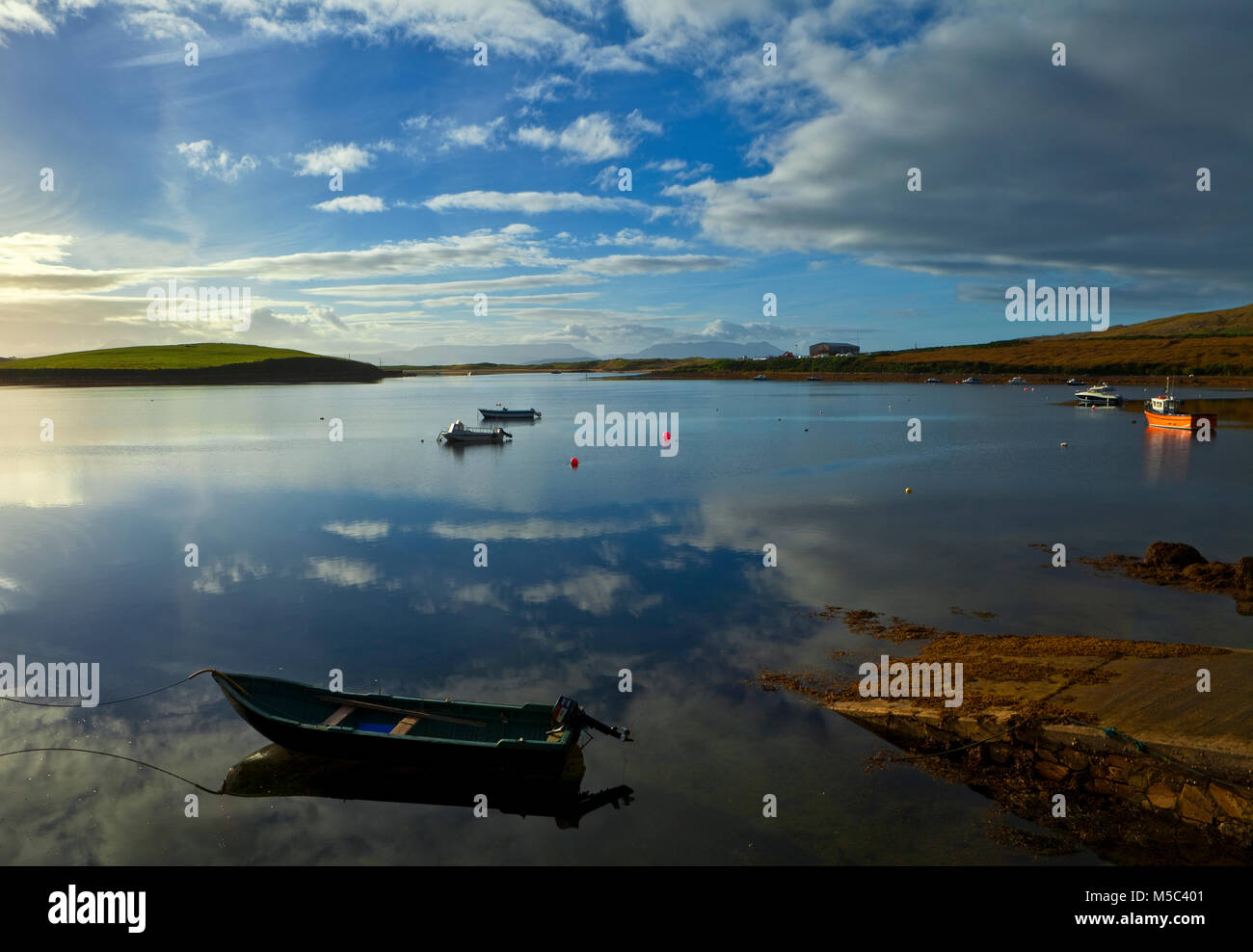 Curragh and rowing boats in  Achill Sound, Achill Island, County Mayo, Ireland - Stock Image