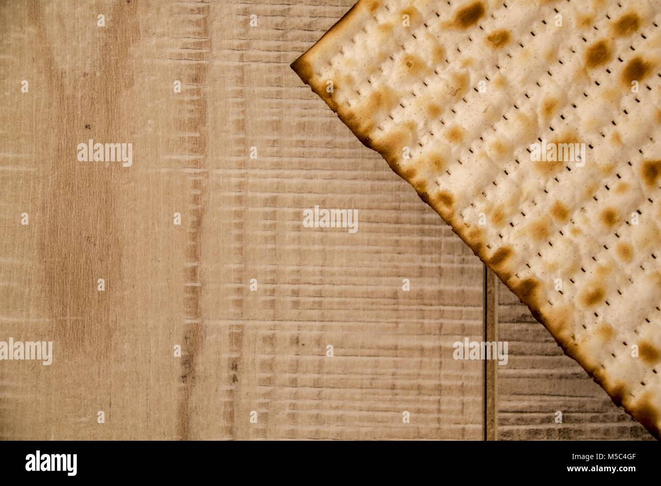 Passover background. Jewish traditional Matzah top view on rustic wooden background with copy-space. Israel national - Stock Image