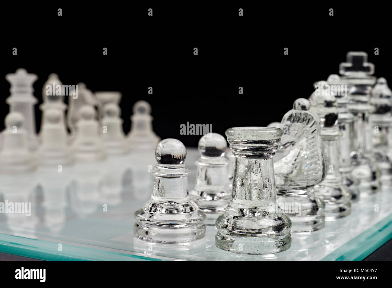 Chess, glass chessboard with pawns on a black background - Stock Image