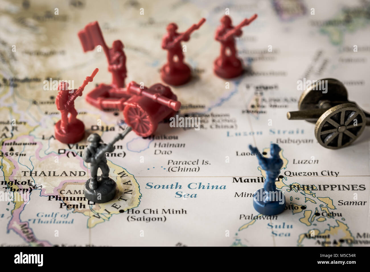 Macro close up of toy soldiers on a map representing conflict and tensions in the South China Sea - Stock Image