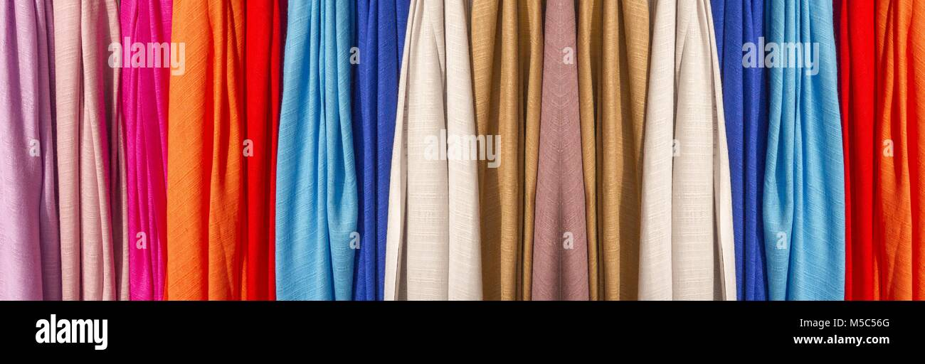 Row of colourful silk scarves hanging at a market .Colorful fabric background, pink gold and blue color silk fabric - Stock Image