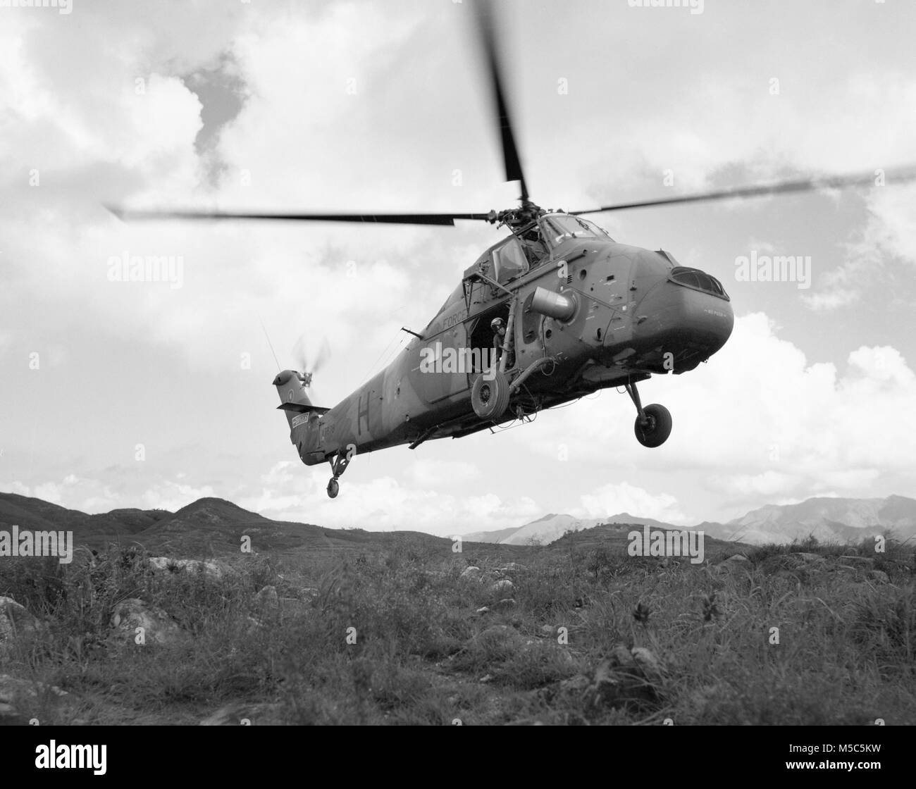 RAF Westland Wessex helicopter of 28 Sqn lifting off in mountainous terrain, Lantau, Hong Kong. - Stock Image