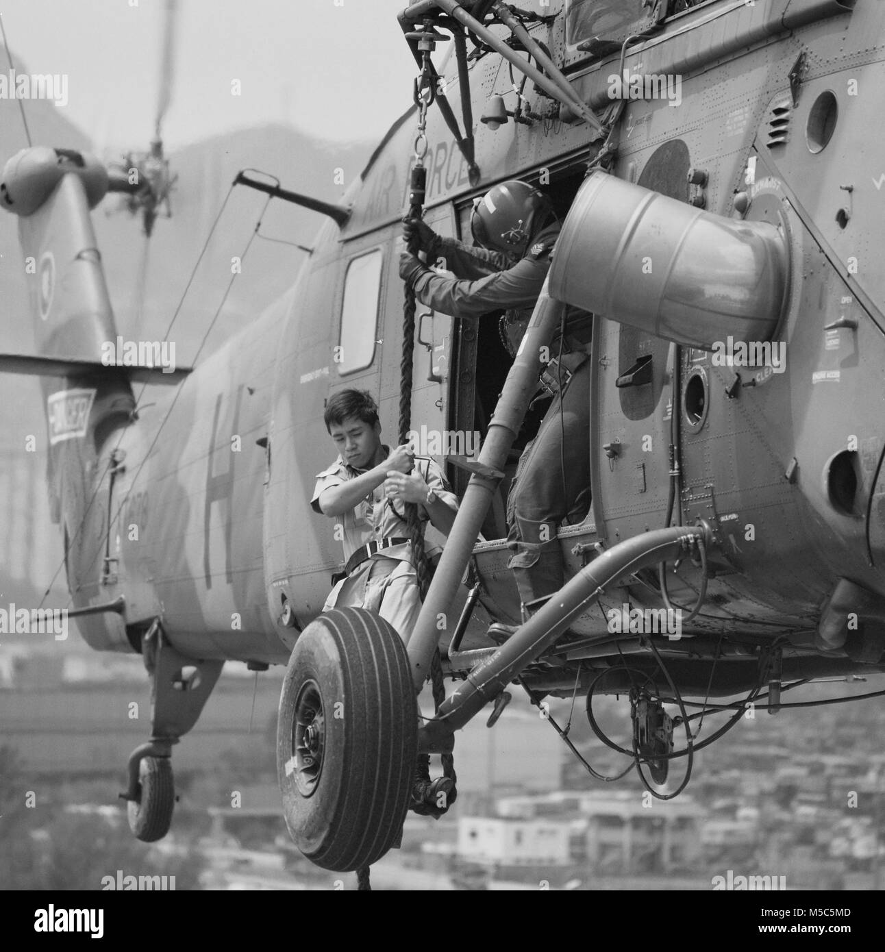 Soldier exiting an RAF Westland Wessex helicopter by rope,Kai Tak, Hong Kong. - Stock Image
