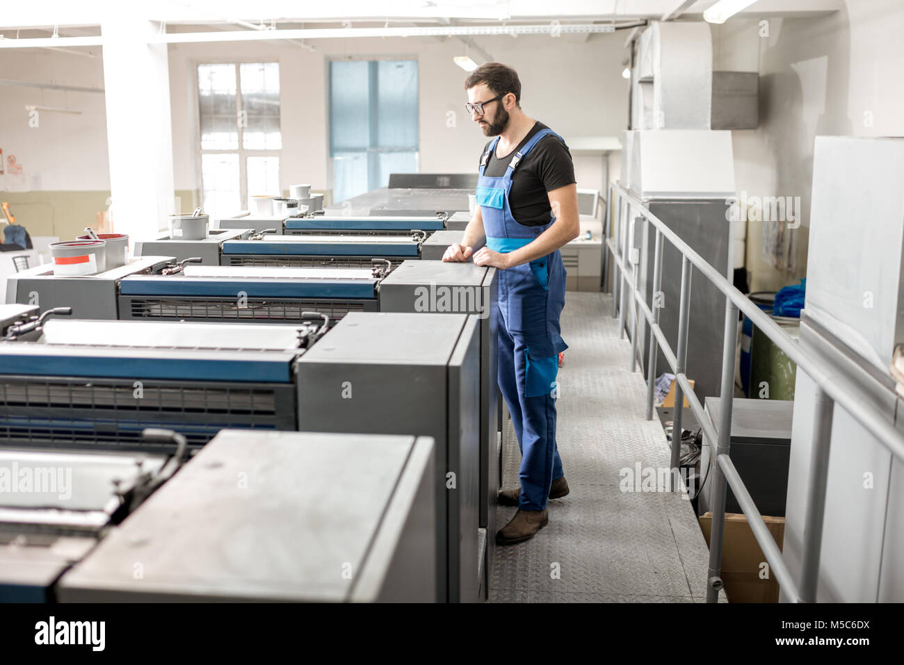 Supervising offset printing machine at the manufacturing - Stock Image