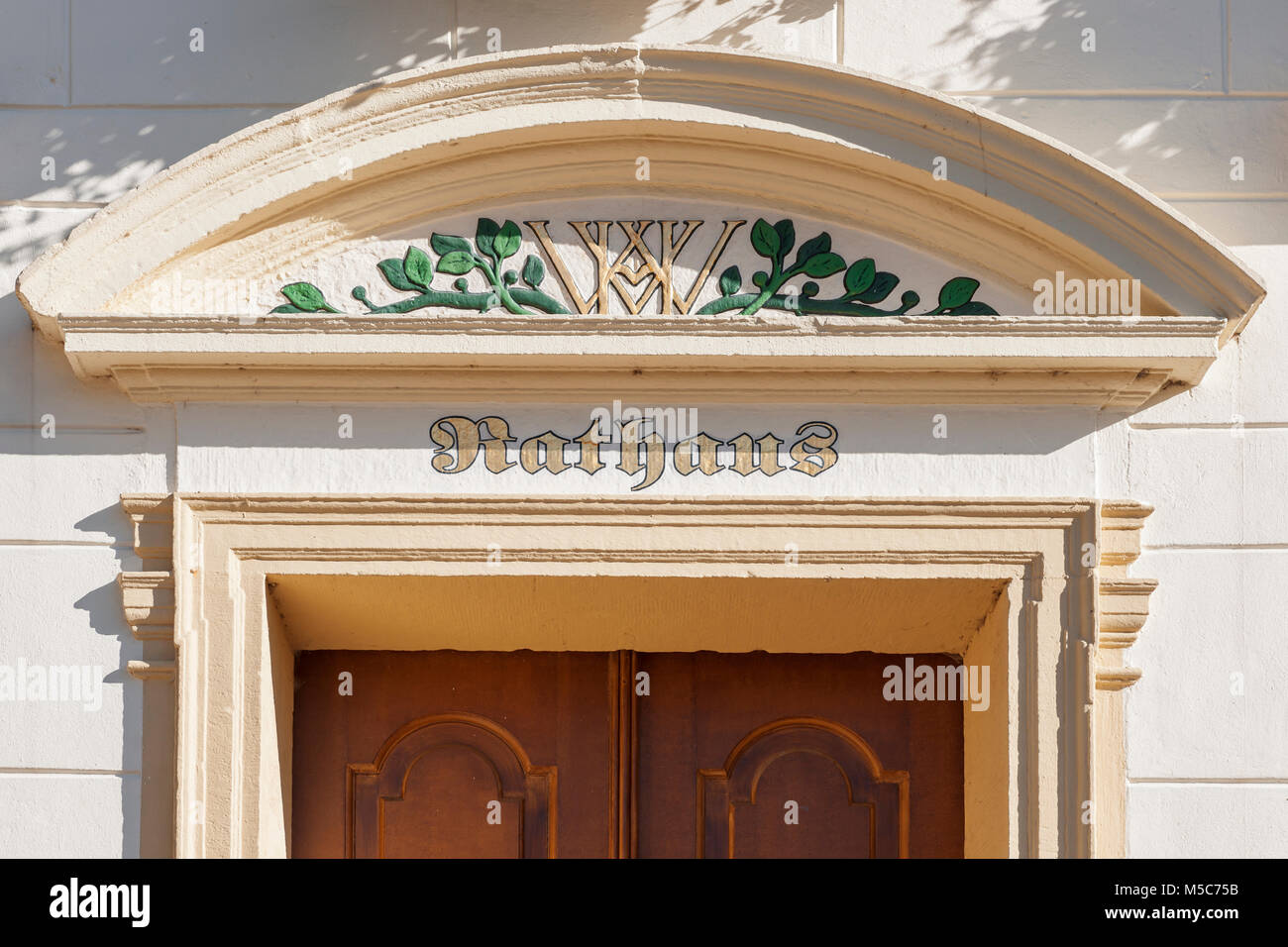 Detailed view of the cornice above the door of the town hall in Esens with tapestry and the initials of the chancellery director of the county of Ol & Detailed view of the cornice above the door of the town hall in ...