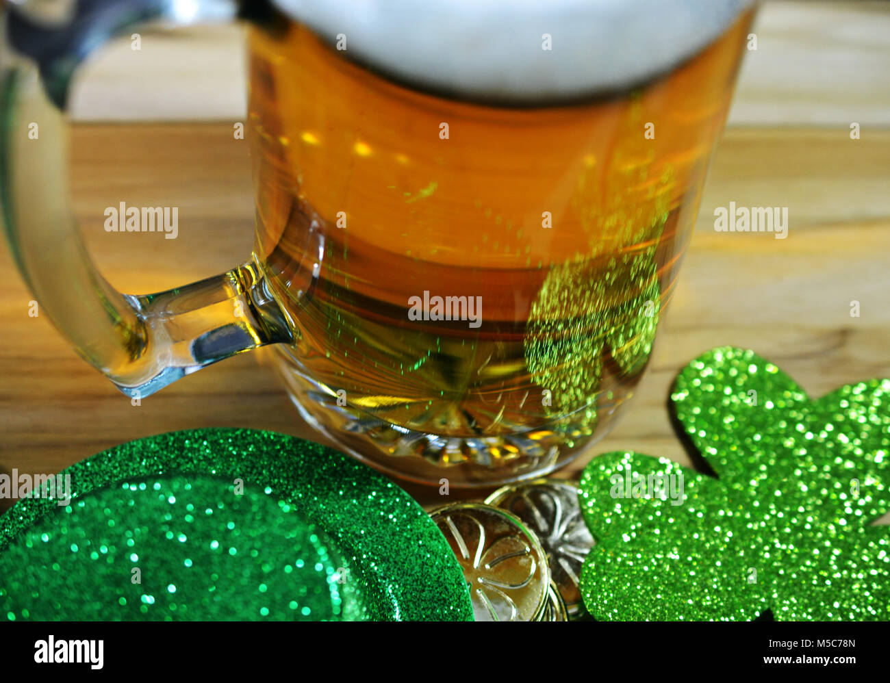 St Patricks Day Glass Beer Stien Filled with Beer showing partial head of foam. Green Top hat, green clo0ver, gold - Stock Image