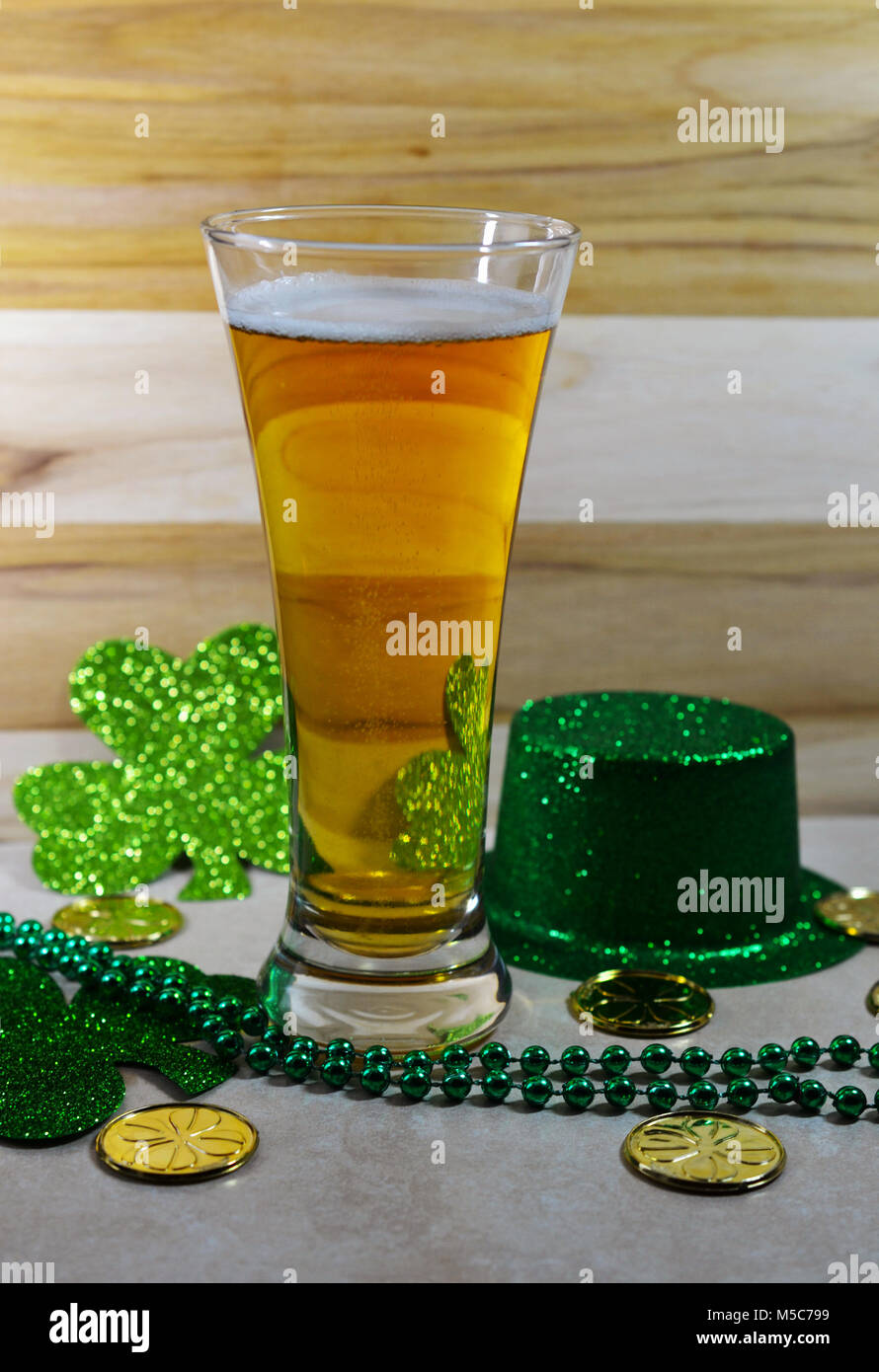 St Patricks Day beer glass filled with beer, thin layer of foam, green top hat, green clover, green stringed beads - Stock Image