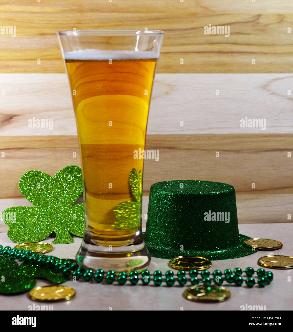 St Patricks Day Traditional beer glass filled with beer, small sliver of foam, green top hat, gree clover, green - Stock Image