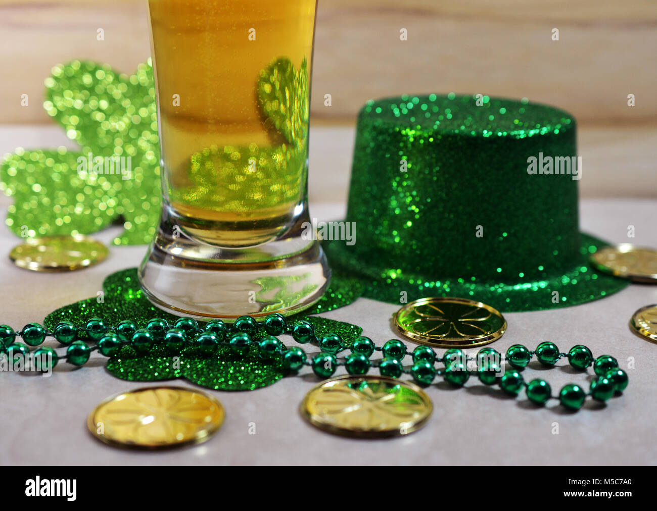 St Patrick's Day Beer glass filled with beer, green beads, gold coins and green top hat. - Stock Image