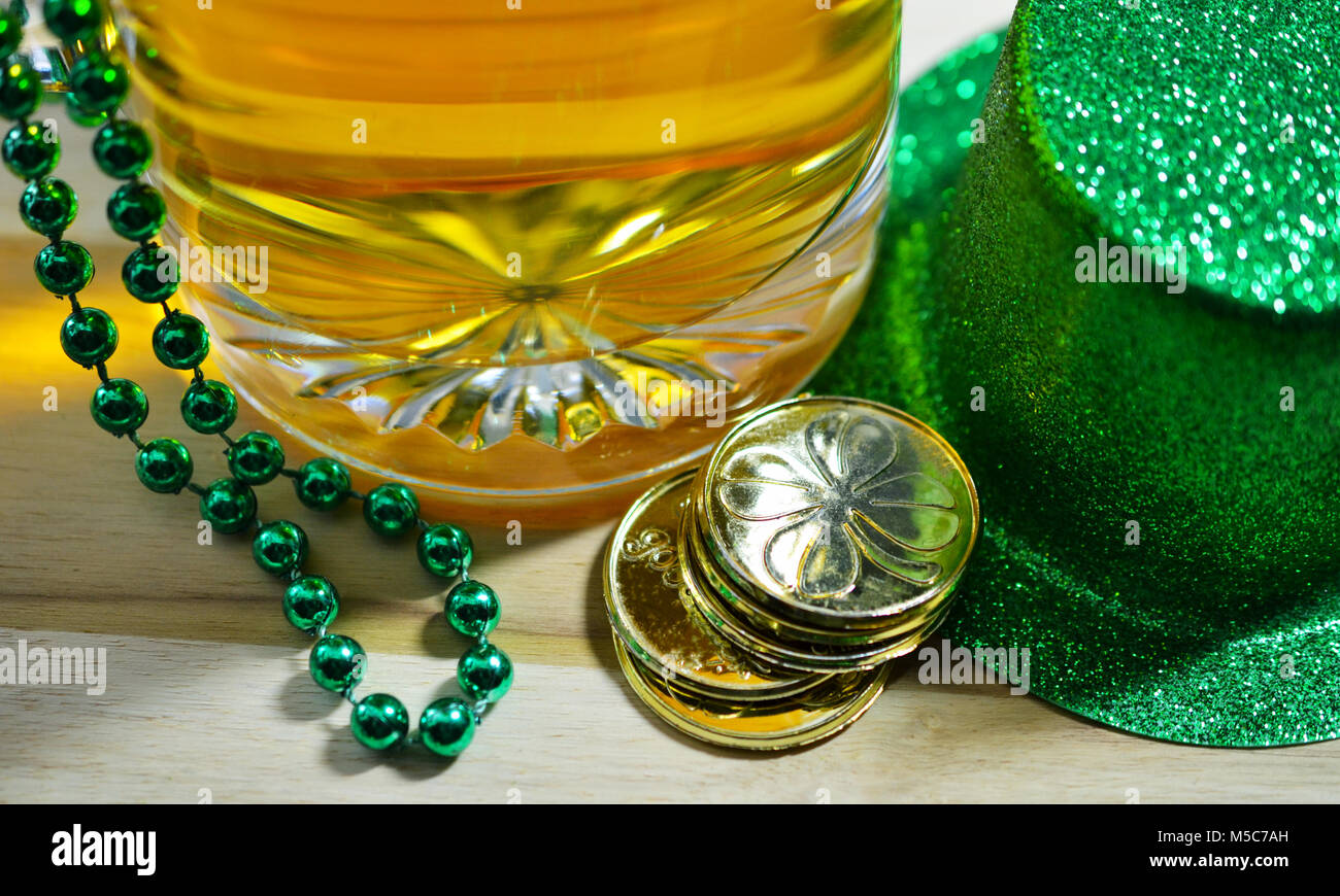 St Patrick's Day Etched Glass Beer Stein filled with Beer, green beads draped over Stein, Gold coins and Irish - Stock Image