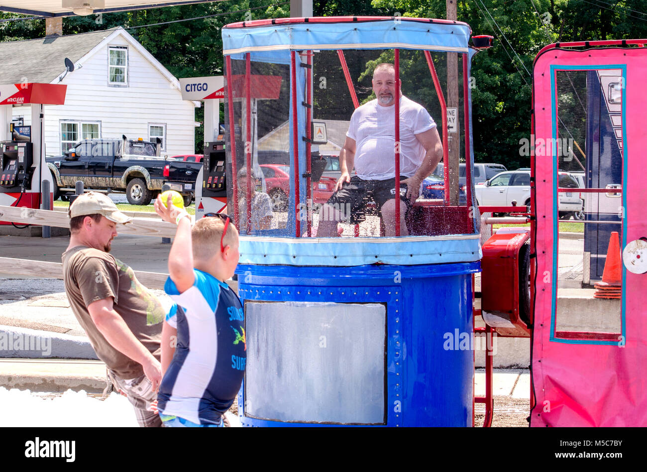 Aug 5, 2017 Michigan USA; a boy prepares to throw a ball, attempting to dunk a man in this wet dunk tank at the - Stock Image