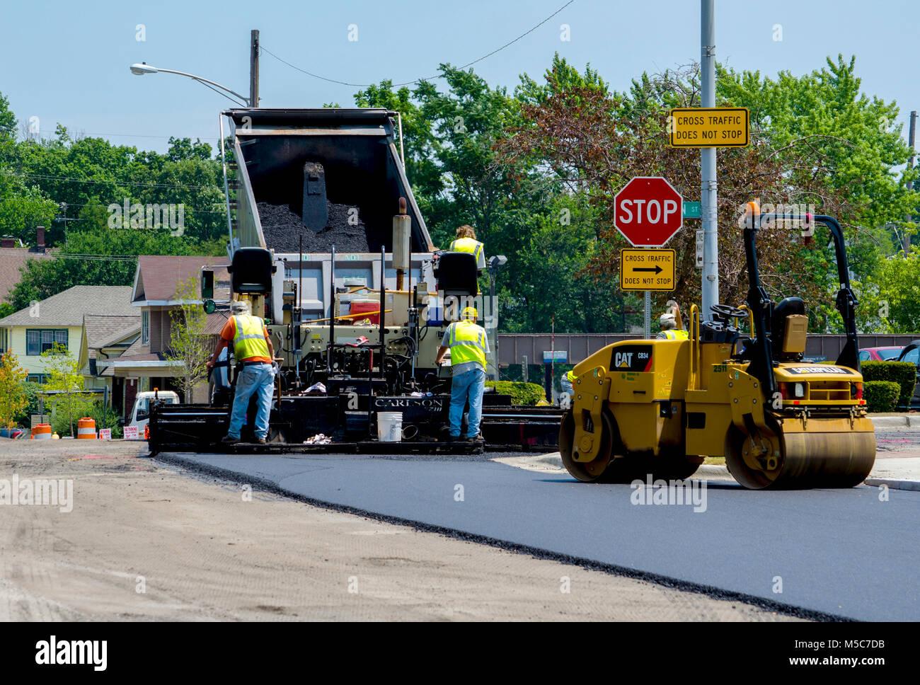 construction road crew work on putting down fresh asphalt on a city street - Stock Image