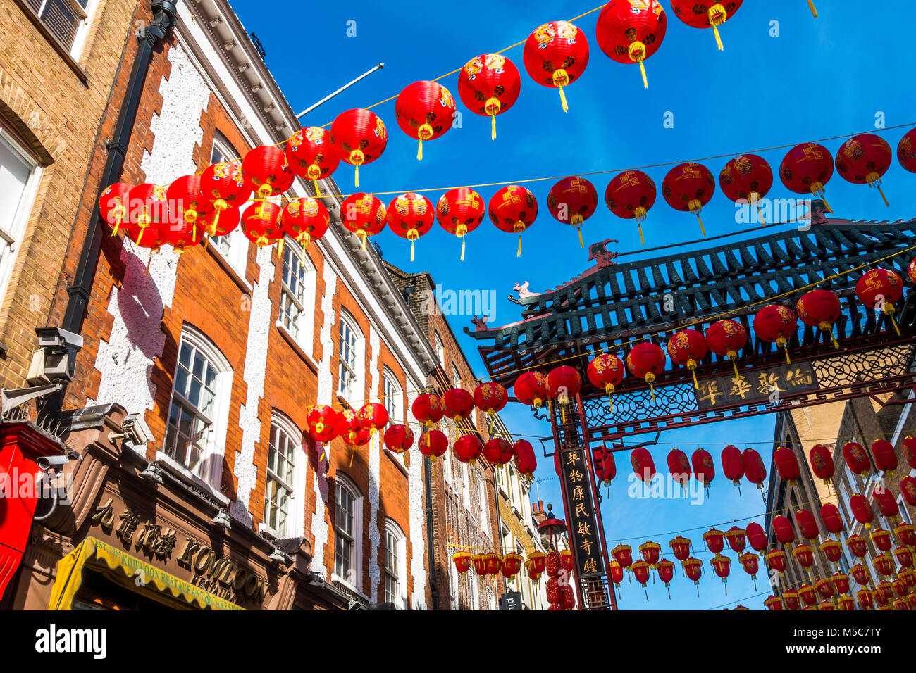 Colourful lanterns against a blue sky, adorning Gerrard Street in Chinatown to celebrate Chinese New Year. Westminster, - Stock Image