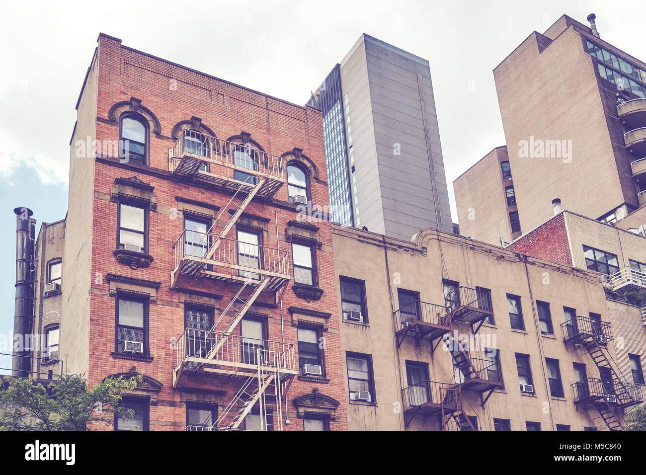 Vintage toned picture of buildings with fire escapes in the New York City, USA. - Stock Image