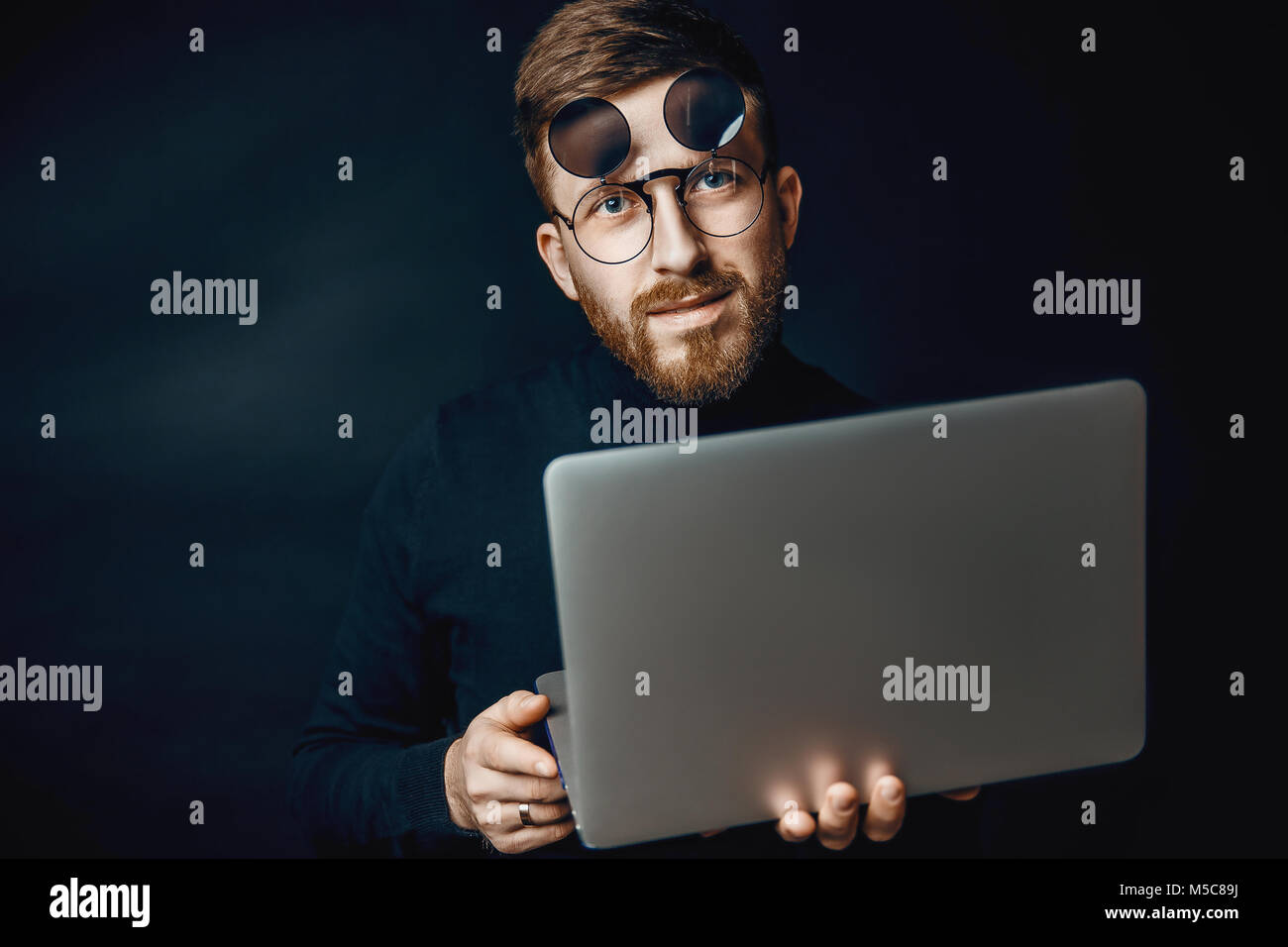 Portrait of handsome brunette bearded man working in office using silver laptop Stock Photo