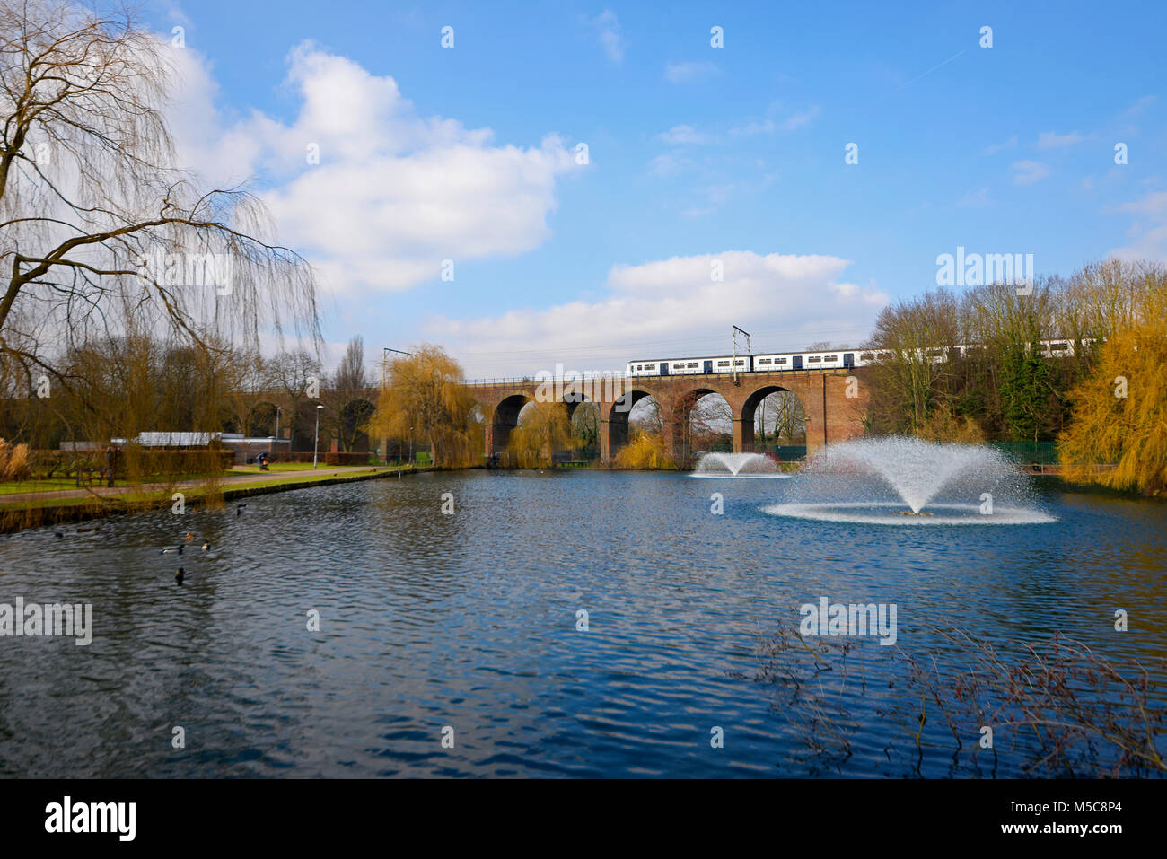 Greater Anglia Abellio electric multiple unit train crossing railway viaduct in Central Park, Chelmsford, Essex, - Stock Image