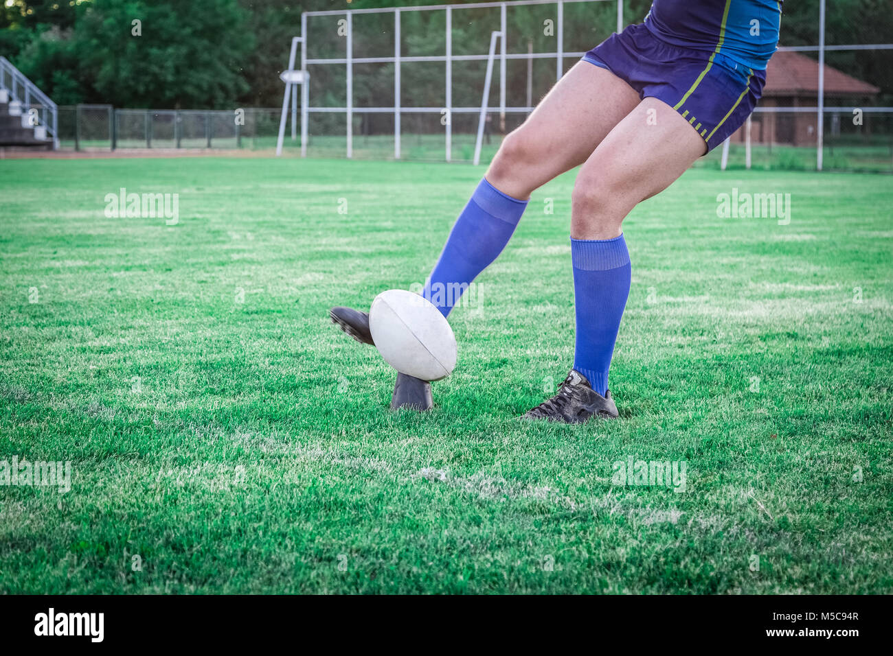 Rugby player kicking the ball for goal at stadium - Stock Image