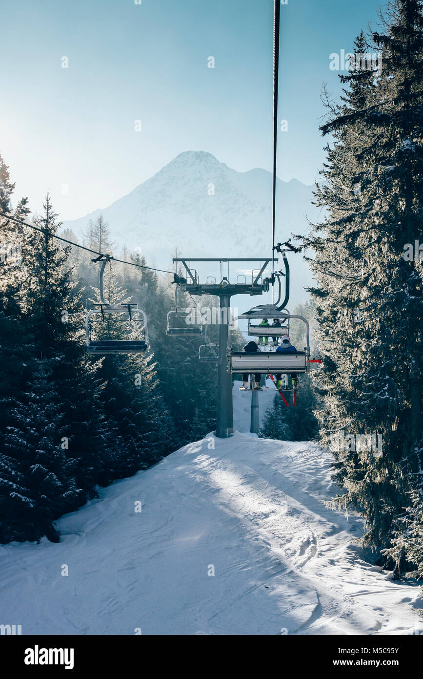 Sun through pine trees as chairlift ascent at Italian ski area covered in snow  - winter sports concept Stock Photo