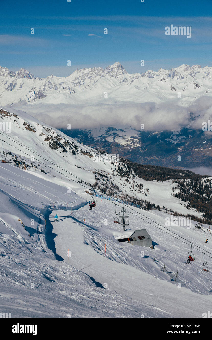Pila, Aosta, Italy - Feb 19, 2018: Chairlift at Italian ski area of Pila on snow covered Alps and pine trees during Stock Photo