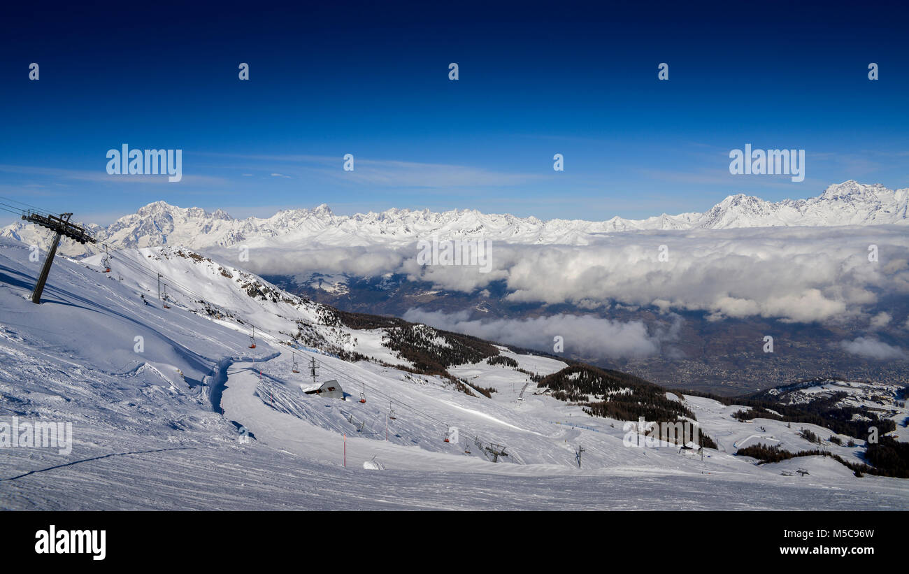 Chairlift at Italian ski area of Pila on snow covered Alps and pine trees during the winter with Mt. Blanc in France Stock Photo