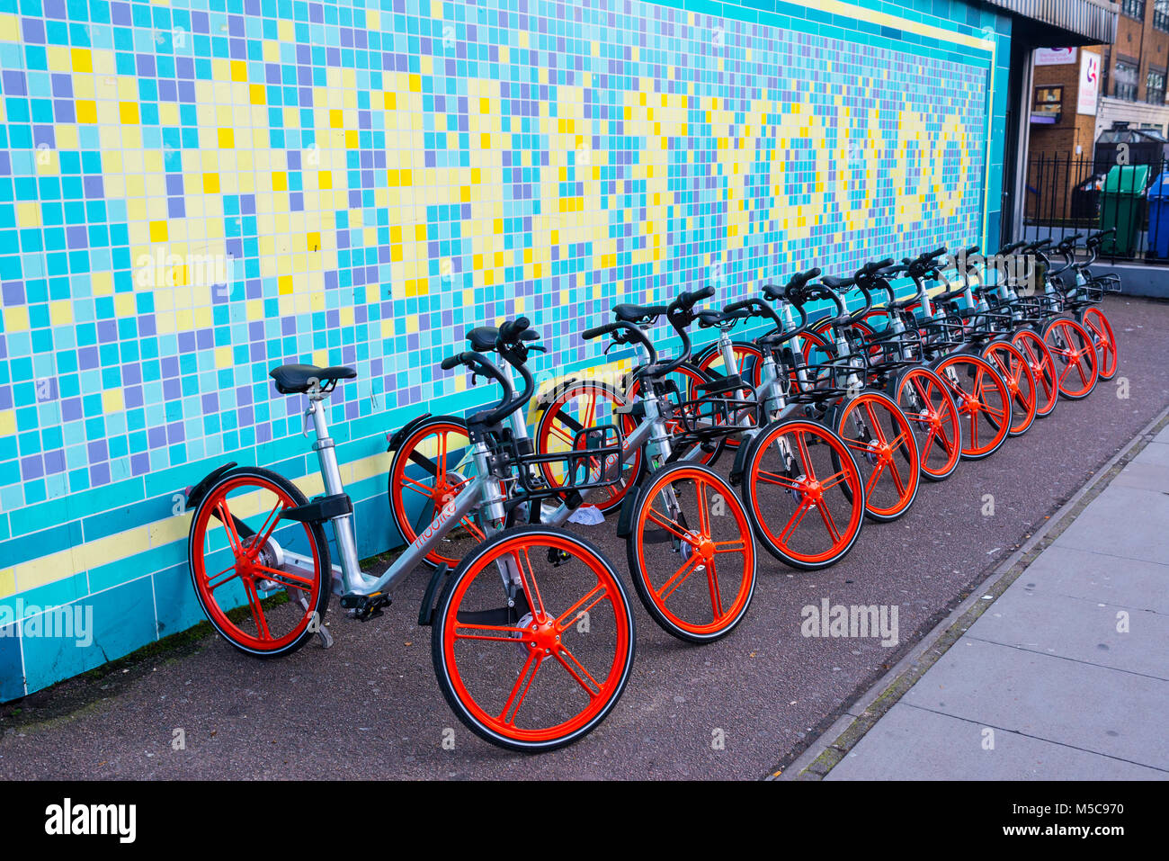 Mobike bicycles parked at a docking station in Torrens street, Angel, London. Mobike is a low cost bike-sharing - Stock Image