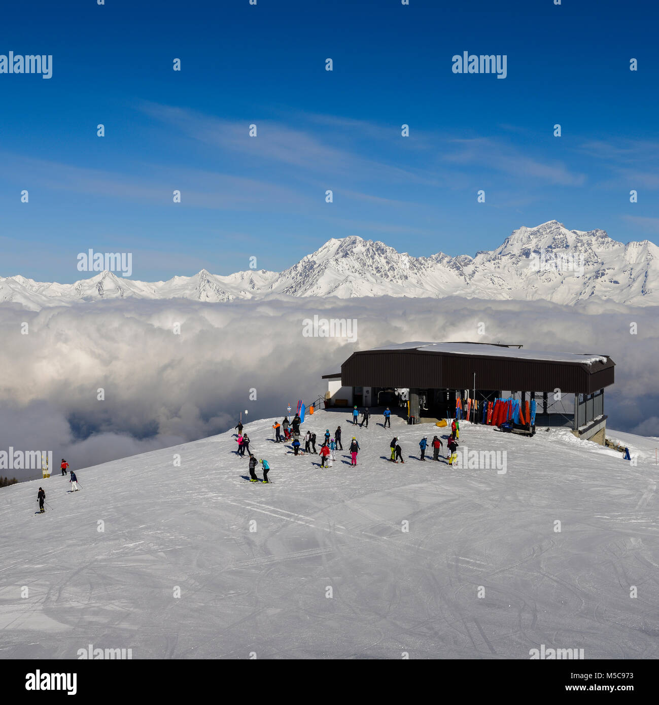 Pila, Aosta, Italy - Feb 19, 2018: Chairlift at Italian ski area of Pila on freshly groomed snow covered Alps above Stock Photo