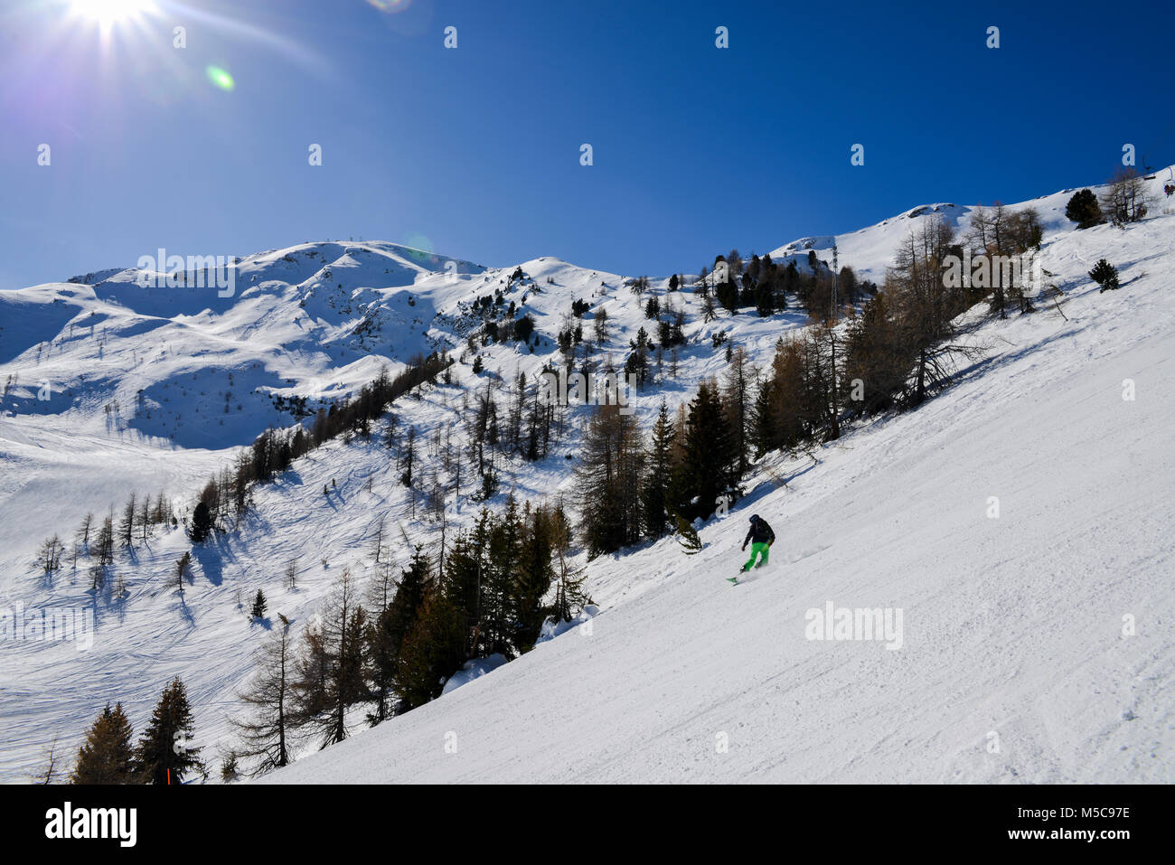 Pila, Aosta, Italy - Feb 19, 2018: Steep gradient piste in Italian Alps with lone expert snowboarder heading down, - Stock Image