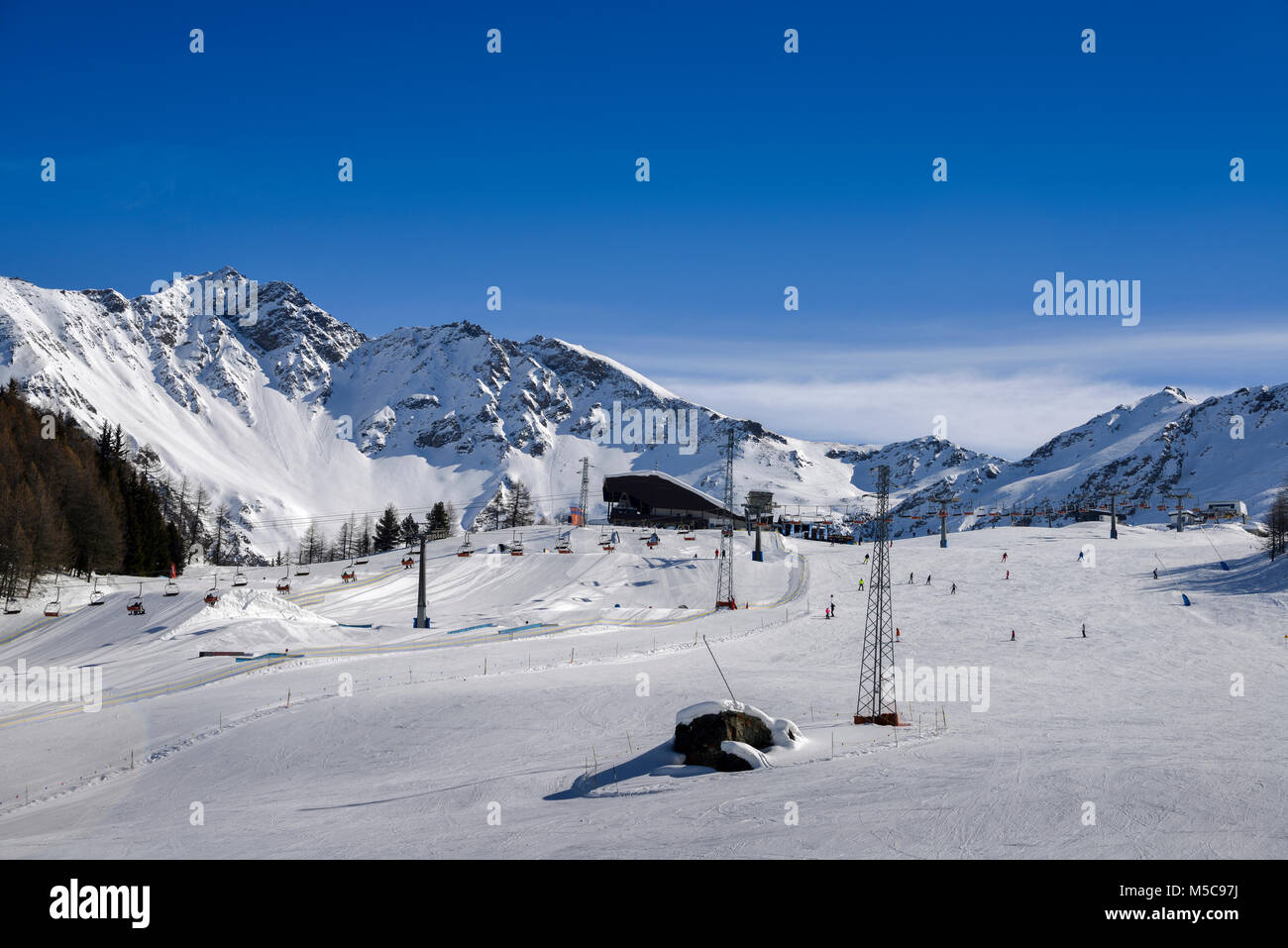 Unidentifiable skiers at ski resort in Pila, Valle d'Aosta, Italy with chairlift and mountain backdrop and copy - Stock Image