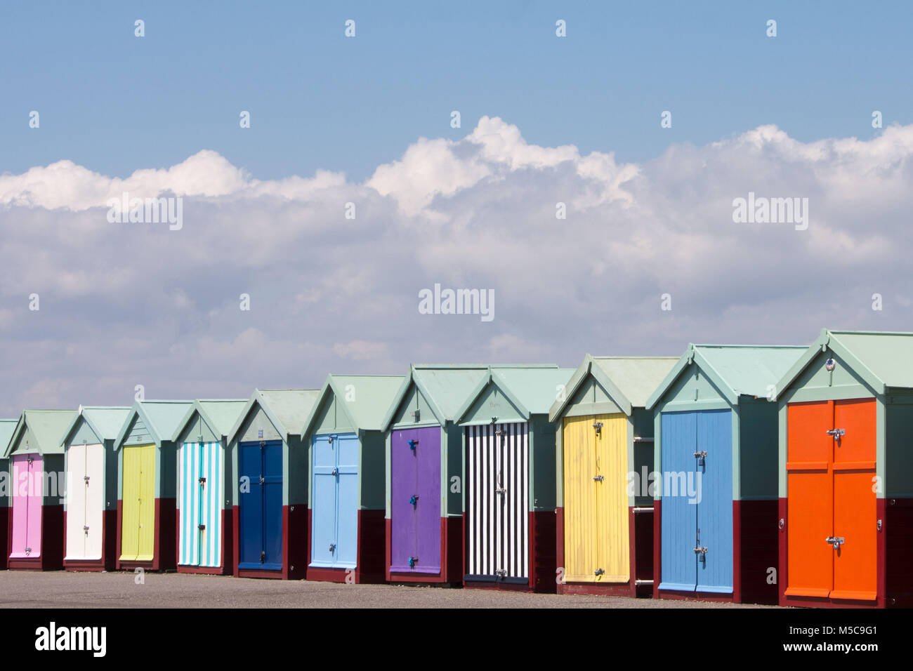A row of colourful beach huts on Hove seafront near Brighton - Stock Image