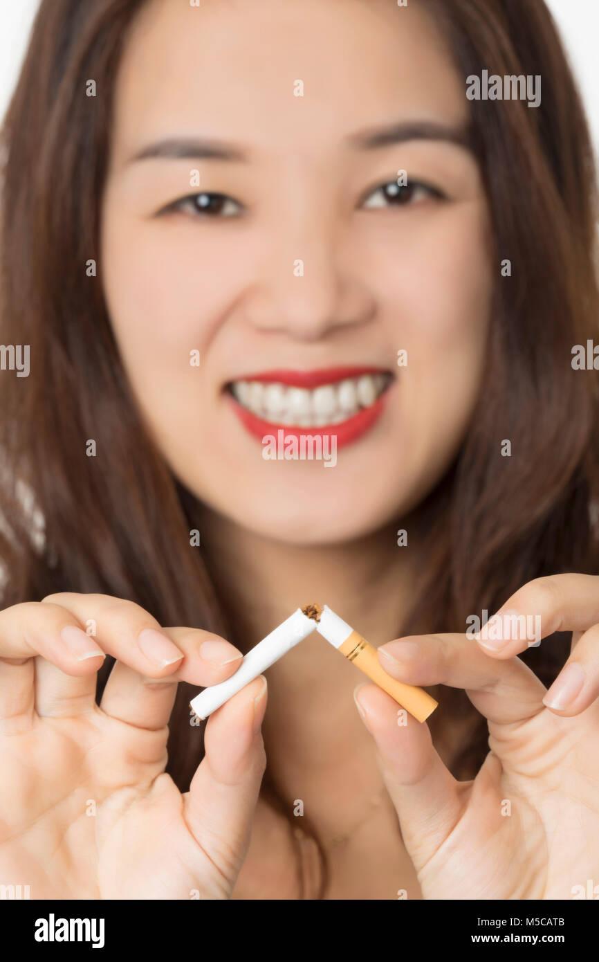 Beautiful Asian woman smiling while breaking a cigarette to quit smoking isolated on a white background - Stock Image