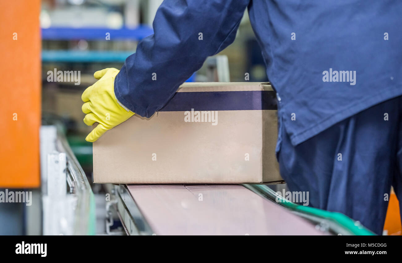 Worker lifting box off production line. Packaging plant with a box being lifted off conveyor belt. - Stock Image