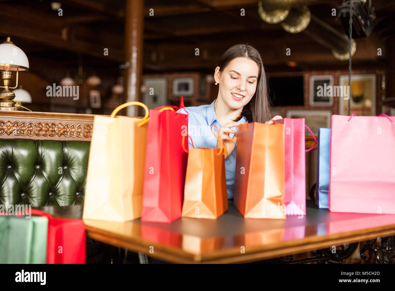 Charming young female watches gifts she bought in a bags - Stock Image