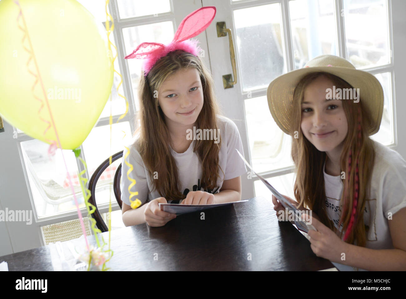 two young children are sitting at a party table eating fried food and drinking milkshakes- there are balloons and - Stock Image
