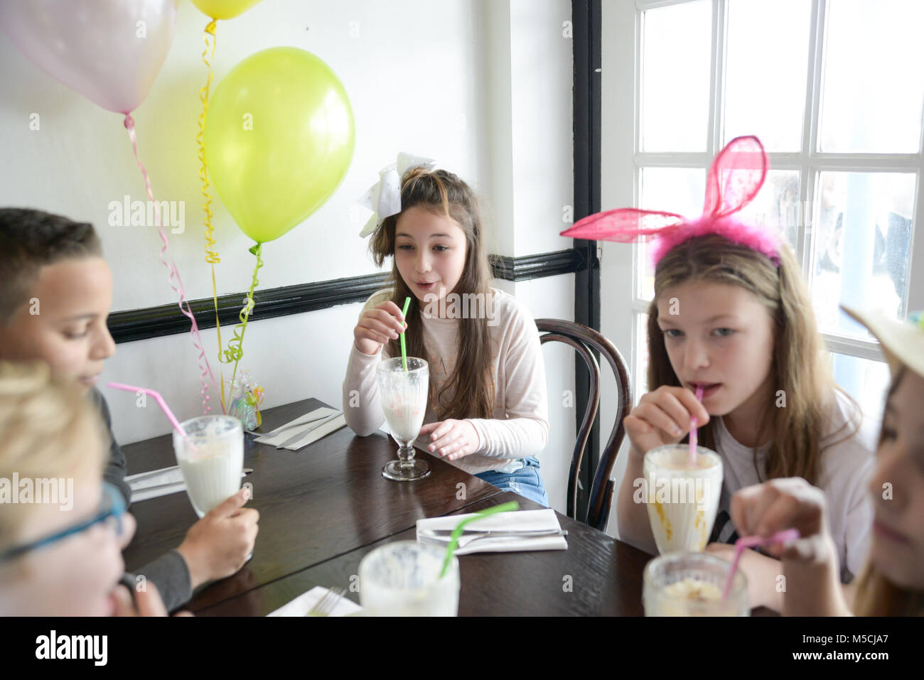 Children at. a party are drinking large milkshakes, there are balloons and table decorations - Stock Image
