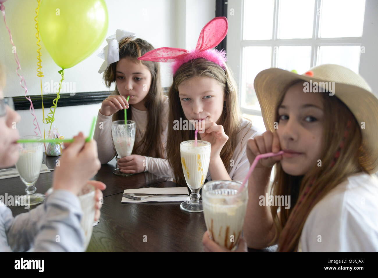 Three young children are sitting at a party table eating fried food and drinking milkshakes- there are balloons Stock Photo