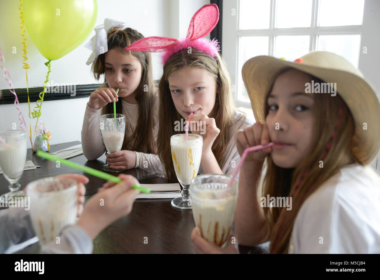Three young children are sitting at a party table eating fried food and drinking milkshakes- there are balloons - Stock Image