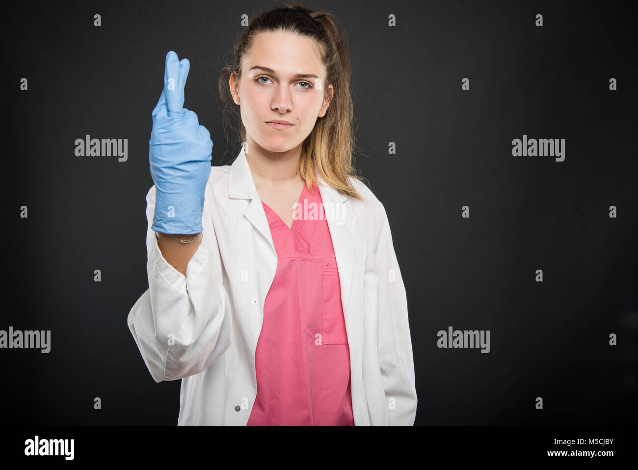 Young doctor portrait  showing fingers crossed wearing sterile gloves on black background with copyspace advertising - Stock Image