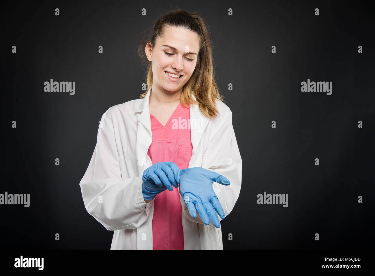 Young female doctor portrait taking her sterile gloves on black background with copyspace advertising area - Stock Image