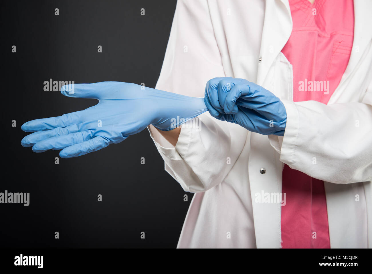 Close-up of doctor putting on her sterile gloves on black background - Stock Image