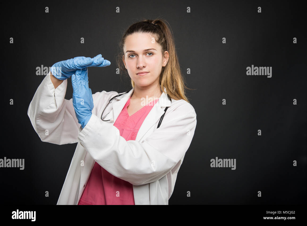 Young doctor portrait  wearing robe showing time out gesture on black background with copyspace advertising area - Stock Image
