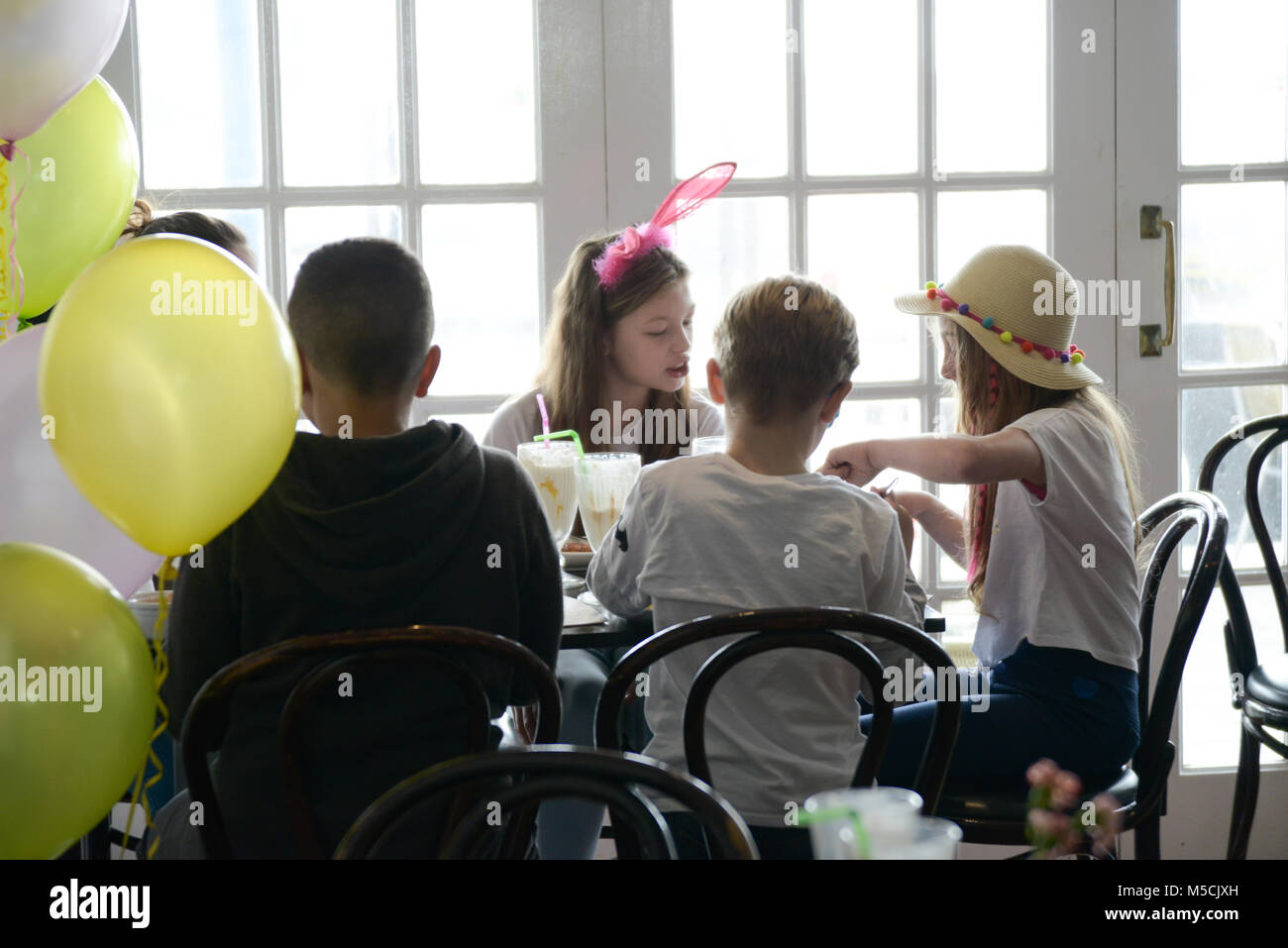 Four young children are sitting at a party table eating fried food and drinking milkshakes- there are balloons and - Stock Image