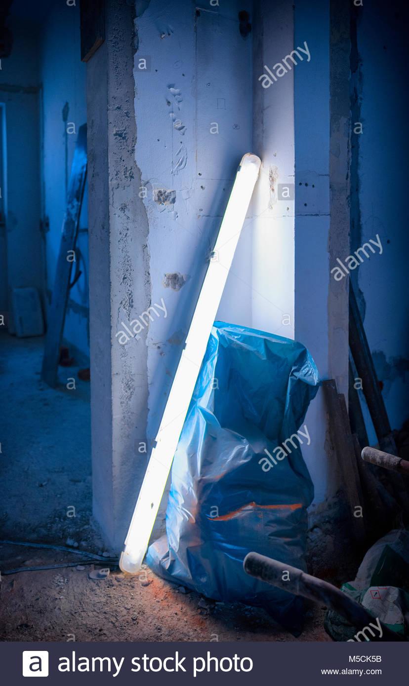 Neon light plastic rubbish bag building site wall - Stock Image