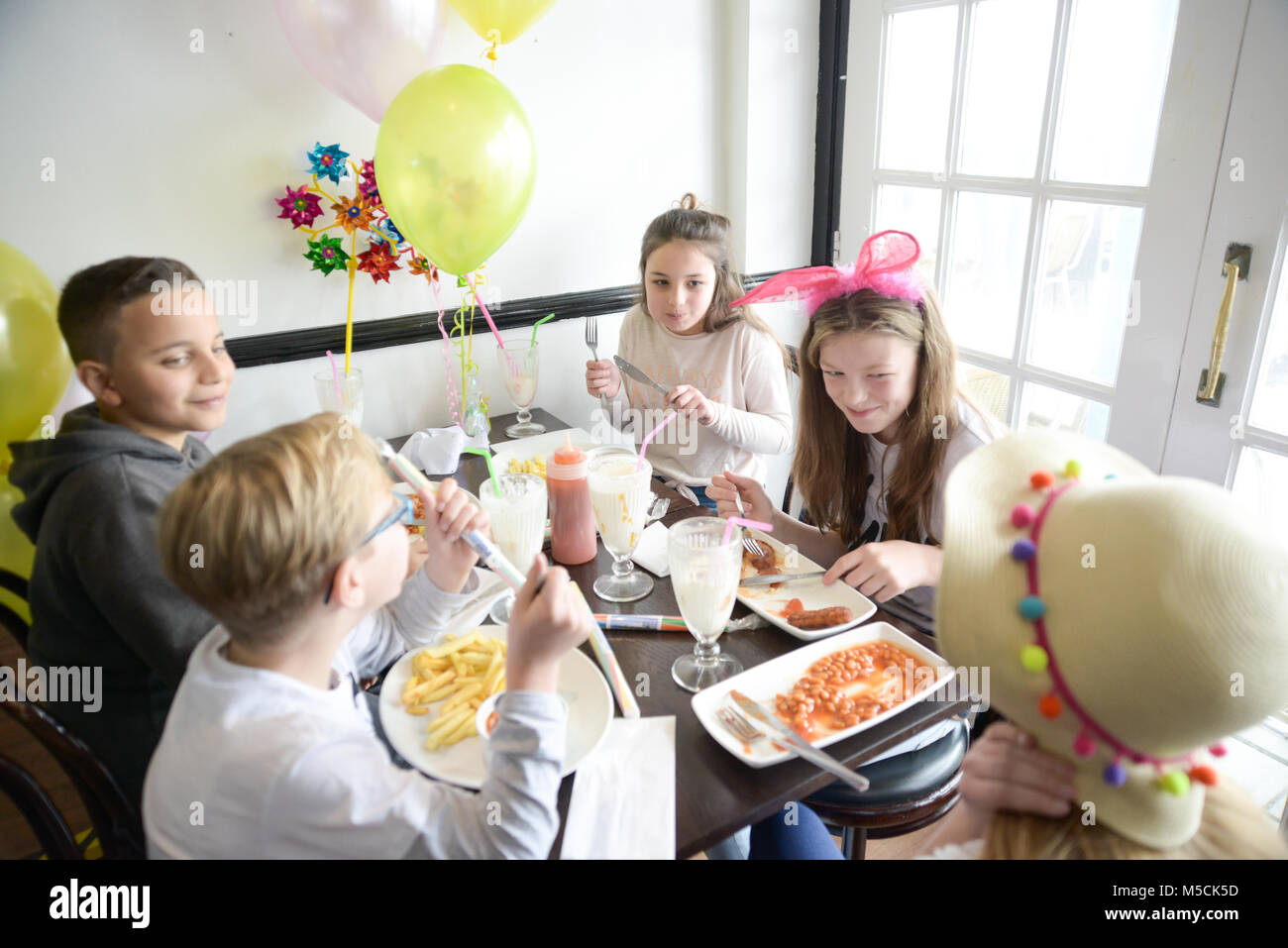 Five young children are sitting at a party table eating fried food and drinking milkshakes- there are balloons and party decorations Stock Photo