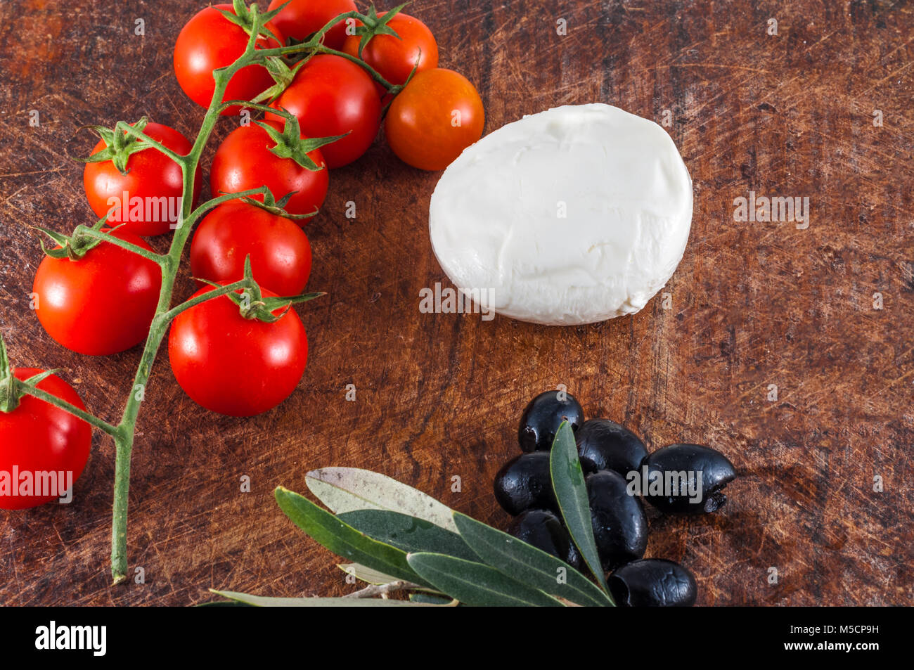 Mozzarella chese, cherry tomatoes and black olives on wooden table - Stock Image