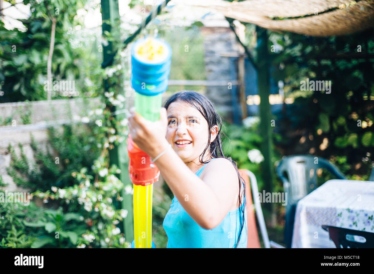 children play in the garden with guns and water rifles on a sunny summer day having a lot of fun - Stock Image